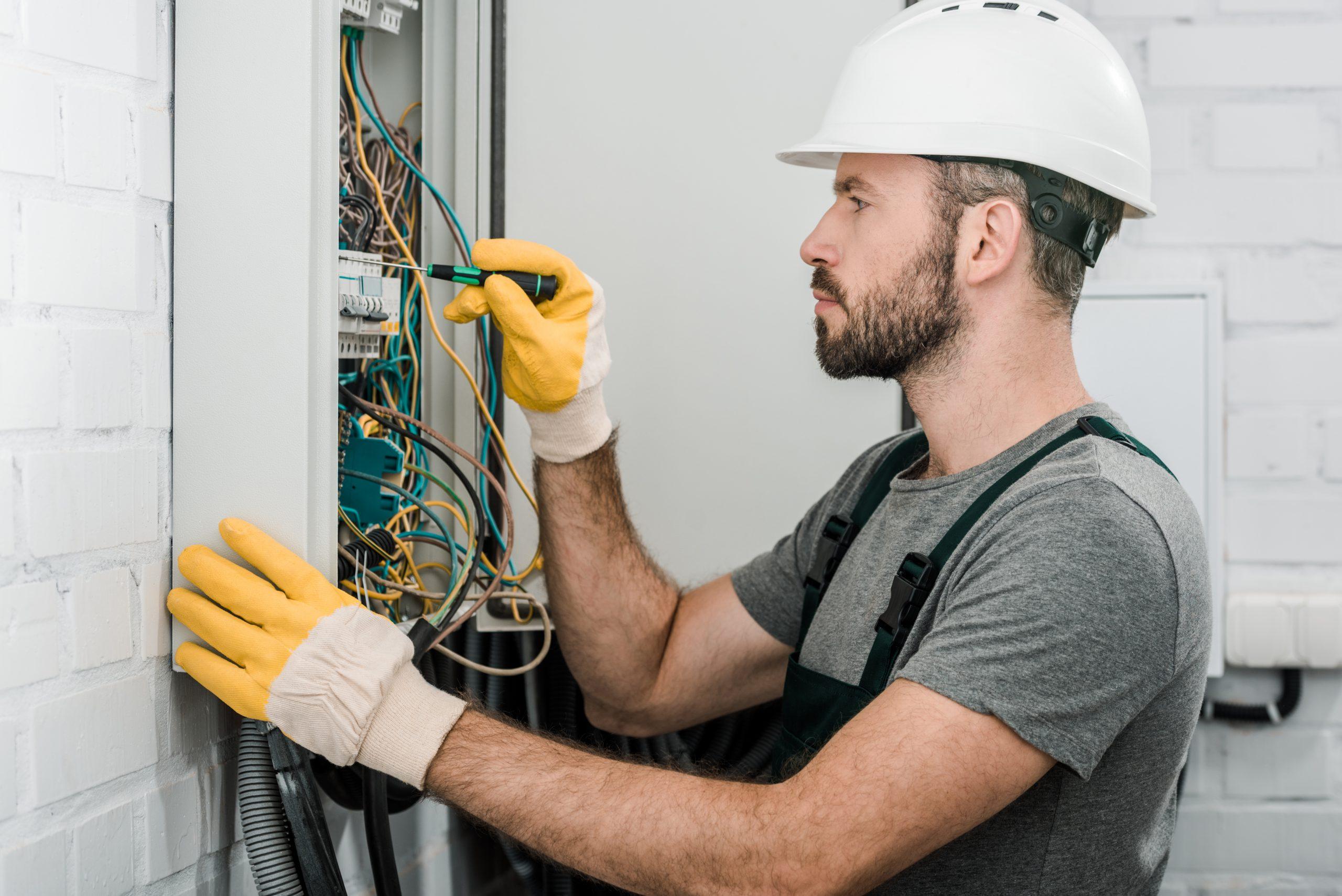 Électricien qui travaille dans un panneau électrique